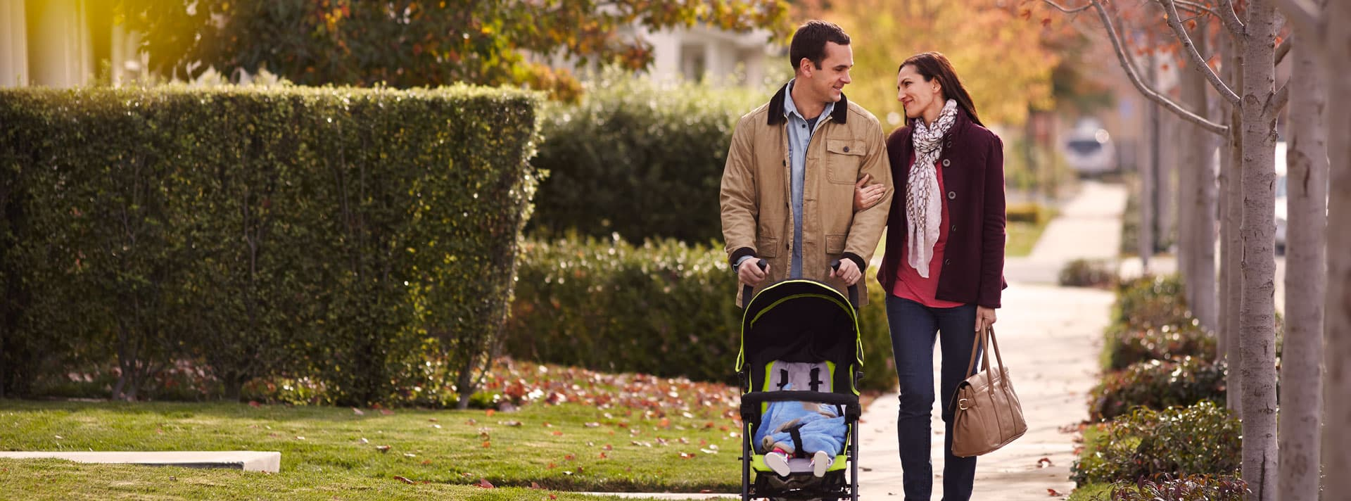 Couple walking with baby stroller
