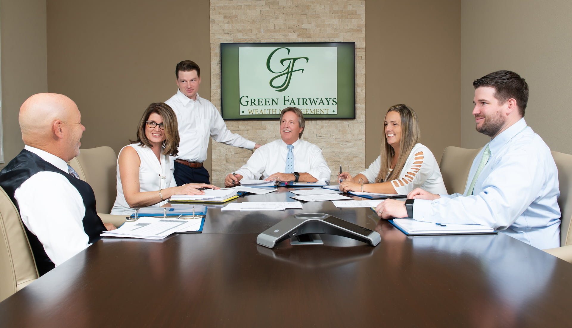 The Green Fairways Wealth Management team sitting around a conference room table